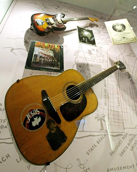"""This March 26, 2012 photo shows a Harmony Sovereign acoustic guitar with a Jesus sticker among other items from Chicano musician Little Willie G, aka Willie Garcia, founding member of Thee Midniters in the 1960s, at the exhibit, """"Trouble In Paradise: Music and Los Angeles, 1945-1975,"""" at the Grammy Museum in Los Angeles. The museum website says the exhibit focuses on the """"tensions between alluring myths of Southern California paradise and the realities of social struggle that characterized the years following WWII."""" (AP Photo/Reed Saxon)"""