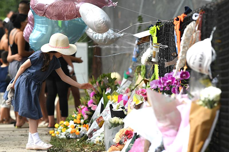 A young girl leaves a tribute at the crash site. Source: AAP