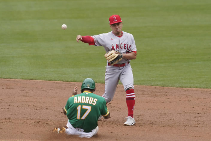 Los Angeles Angels' Kean Wong, top, throws to first base after forcing out Oakland Athletics' Elvis Andrus (17) at second base on a double play hit into by Aramis Garcia during the third inning of a baseball game in Oakland, Calif., Saturday, May 29, 2021. (AP Photo/Jeff Chiu)