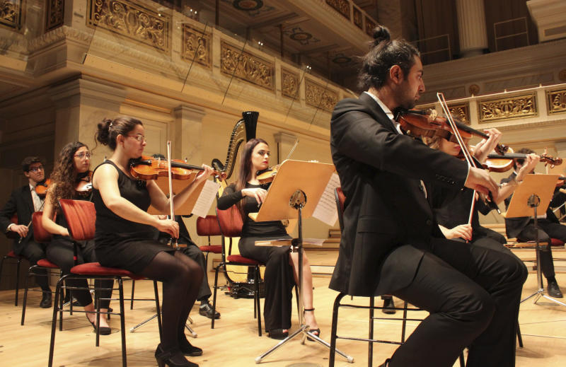 In this Sept. 11, 2016 photo musicians of the Syrian Expat Philharmonic Orchestra perform in the Concert House in Berlin's Gendarmenmarkt. The Orchestra consists entirely of professional musicians who fled civil war in their homeland to seek refuge in Europe. (AP Photo/Jona Kallgren)