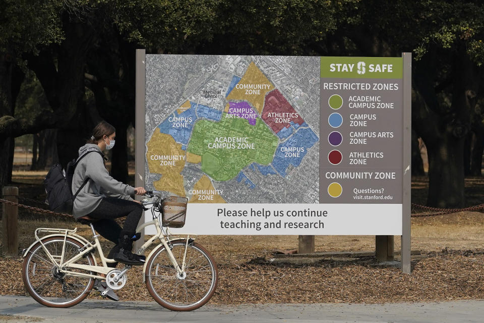 A bicyclist rides past a sign showing restricted zones around the Stanford University campus in Stanford, Calif., Wednesday, Sept. 2, 2020. With the coronavirus spreading through colleges at alarming rates, universities are scrambling to find quarantine locations in dormitory buildings and off-campus properties to isolate the thousands of students who have caught COVID-19 or been exposed to it. (AP Photo/Jeff Chiu)