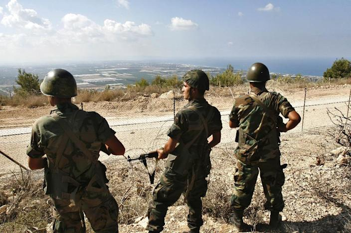 FILE - In this Monday, Oct. 2, 2006 file photo, Lebanese soldiers guard the Lebanese side of the border fence, as they look towards northern Israel, in the southern village of Labbouneh, a day after the Israeli army withdrew from the entire south except for the village of Ghajar. An explosion on Wednesday wounded Israeli soldiers who had crossed the border into Lebanon in a rare incident on the heavily guarded and volatile frontier, a Lebanese army statement said. (AP Photo/Mohammed Zaatari, File)