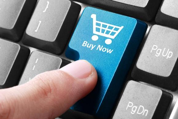 A finger pressing a blue button on a computer keyboard with the words Buy Now on it.