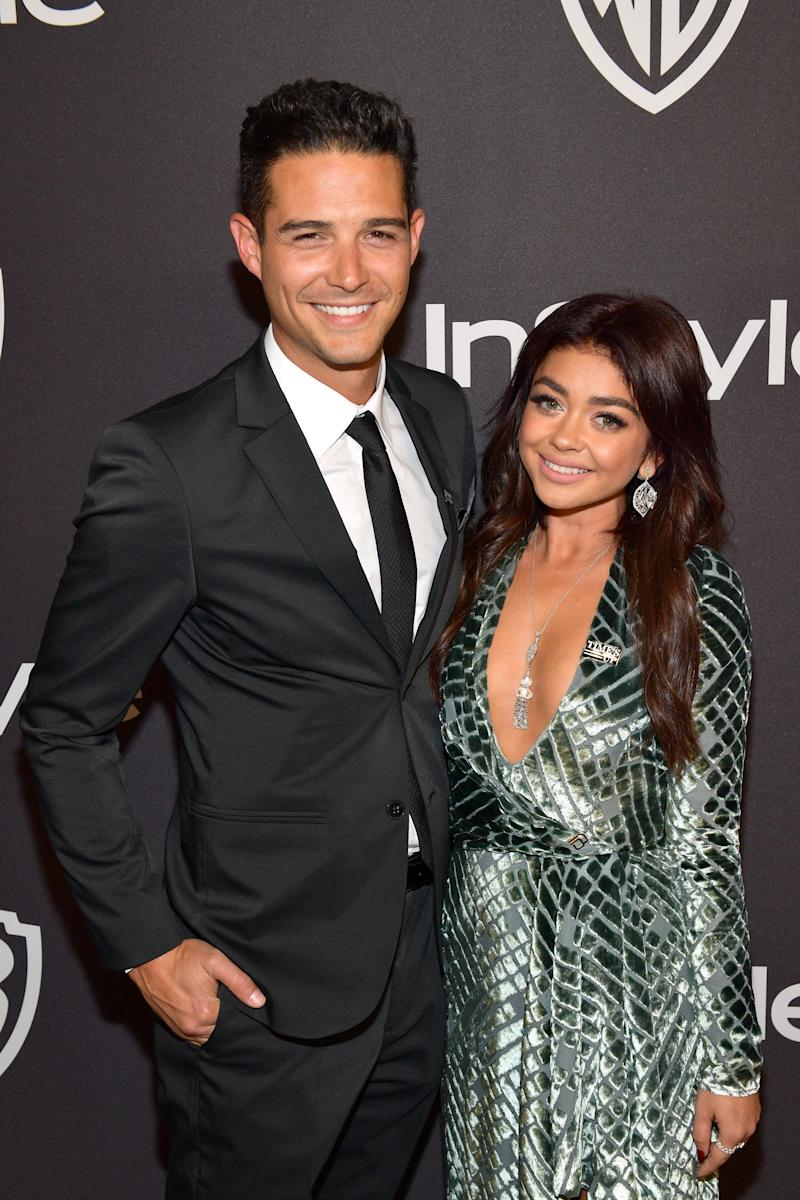 Wells Adams and fiance, Sarah Hyland look stunning on the red carpet in black suit and green dress as they smile brightly for the camera