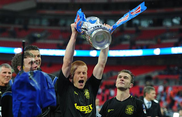 Match-winner Ben Watson celebrates with the FA Cup after Wigan beat Manchester City (Photo credit should read ANDREW YATES/AFP/Getty Images)