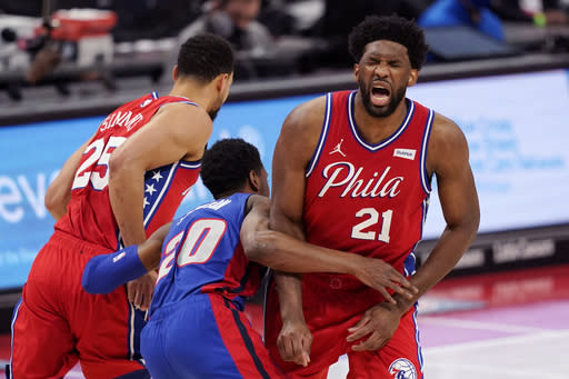 Philadelphia 76ers center Joel Embiid (21) grimaces after Detroit Pistons guard Josh Jackson (20) runs into him after chasing guard Ben Simmons (25) during the first half of an NBA basketball game, Saturday, Jan. 23, 2021, in Detroit. (AP Photo/Carlos Osorio)