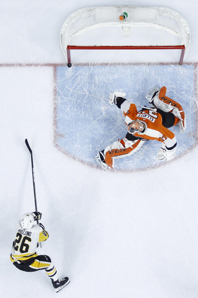 Pittsburgh Penguins' Andrew Agozzino (26) cannot get a shot past Philadelphia Flyers' Brian Elliott (37) during the first period of an NHL hockey game, Tuesday, Jan. 21, 2020, in Philadelphia. (AP Photo/Matt Slocum)
