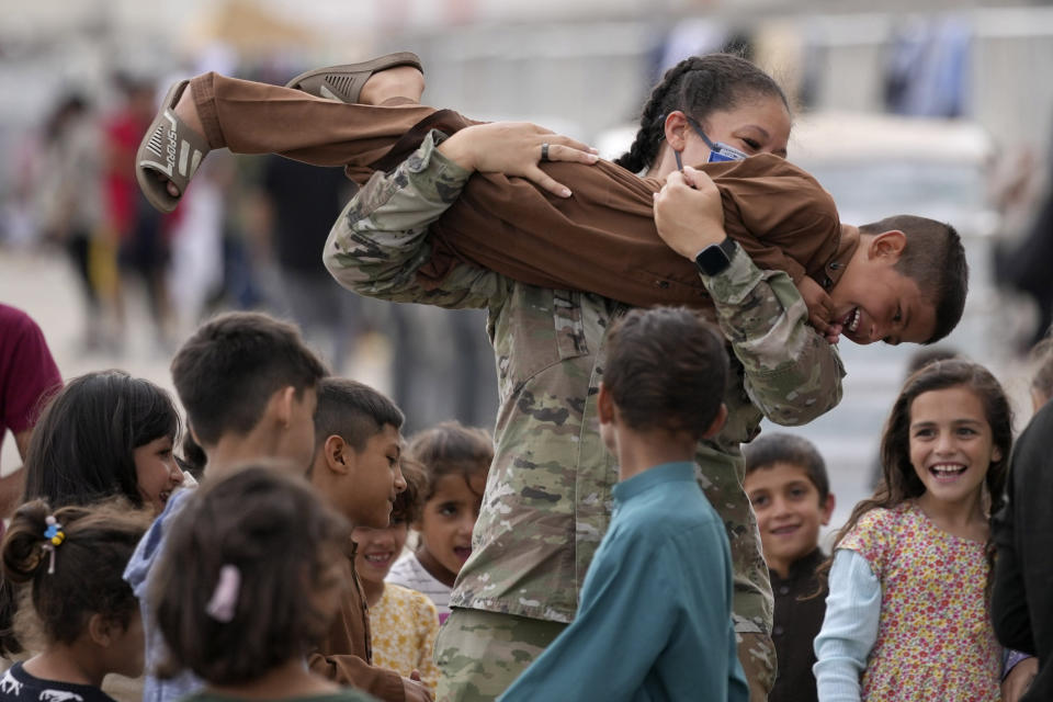 An U.S. soldier plays with recently evacuated Afghan children at the Ramstein U.S. Air Base, Germany, Tuesday, Aug. 24, 2021.The largest American military community overseas housed thousands Afghan evacuees in an increasingly crowded tent city. (AP Photo/Matthias Schrader)