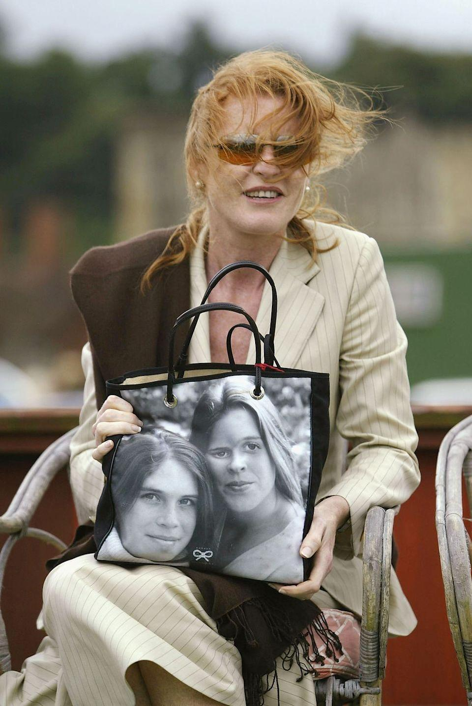 <p>In classic mom fashion, Sarah Ferguson shows off a bag printed with a photo of her daughters, Princesses Eugenie and Beatrice, at the Cowdray Park Polo Club. </p>