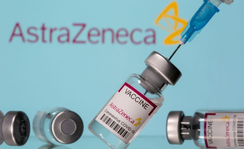 """FILE PHOTO: Vials labelled """"Astra Zeneca COVID-19 Coronavirus Vaccine"""" and a syringe are seen in front of a displayed AstraZeneca logo in this illustration photo"""