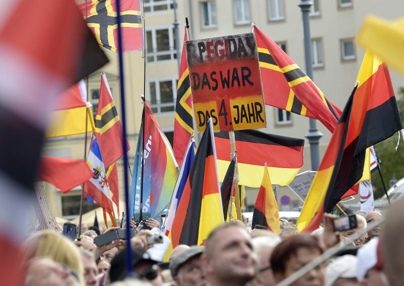"People carry a sign reading ""PEGIDA that was your fourth year"" during a rally of PEGIDA (Patriotic Europeans against the Islamization of the West) in Dresden, Germany, Sunday, Oct.21, 2018. (AP Photo/Jens Meyer)"