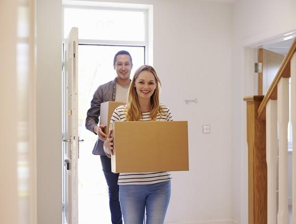 A young couple carrying boxes into a new home