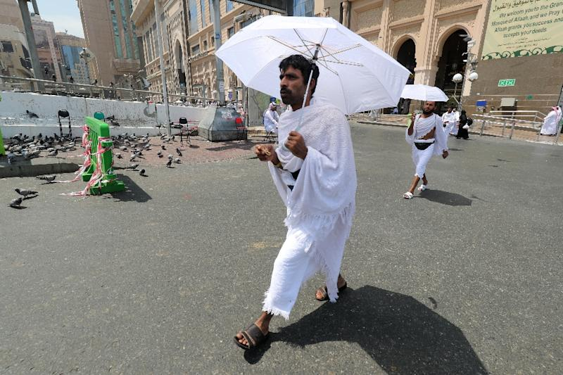 Muslim pilgrims carry umbrellas to protect themselves from the sun in Saudi Arabia's holy city of Mecca on August 19, 2018 (AFP Photo/AHMAD AL-RUBAYE)