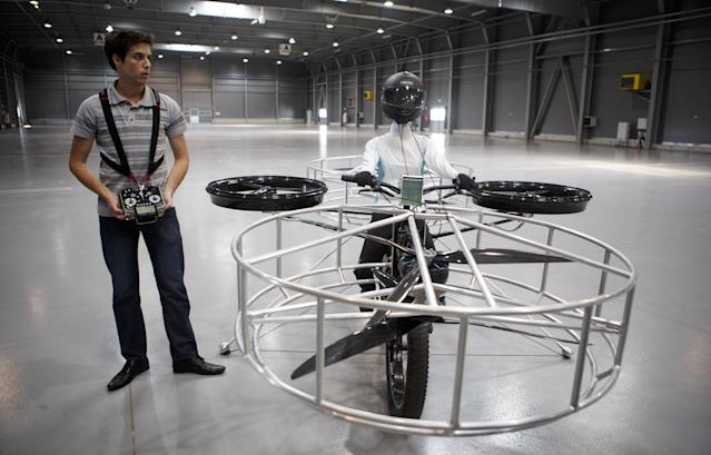 A technician holds the remote control for a 'Flying bike' bicycle after its first public flight on June 12, 2013 in Prague, Czech Republic. The bike has been manufactured by 3 different companies from the Czech Republic (Duratec, Technodat, Evektor) and has been supported by French Company Dassault System. The F-Bike has four main motors (10kW) and two stabilization motors (3,5 kW). It has an estimated constant flight time of 3-5 minutes. (Photo by Matej Divizna/Getty Images)