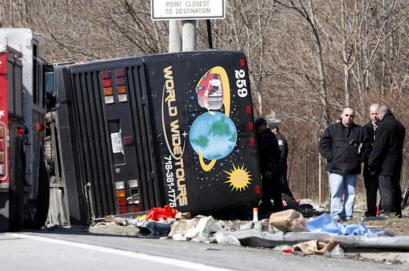FILE--In this photo from Saturday, March 12, 2011, emergency personnel investigate the scene of a bus crash on Interstate-95 in the Bronx borough of New York. A verdict has been reached in a manslaughter case against the bus driver Ophadell Williams, charged in the crash that killed 15 passengers.  Williams has pleaded not guilty. He says a tractor-trailer cut him off and he lost control. The bus carrying gamblers coming from a Connecticut casino was sheared open like a sardine can when it struck a pole.  (AP Photo/David Karp, File)