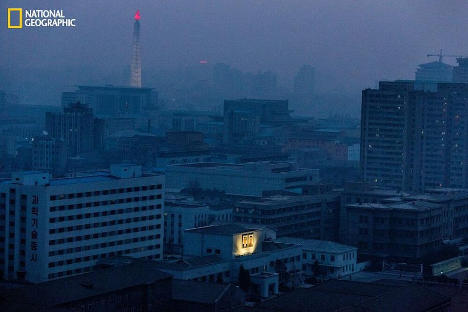 At dawn, portraits of Kim Il Sung and his son Kim Jong Il are still lit up in Pyongyang. Even during the city's blackouts, electricity is reserved to light the flame atop Juche Tower. (David Guttenfelder/National Geographic)