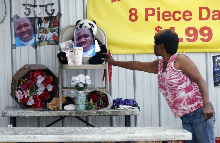 Nishka Johnson touches a makeshift memorial for Alton Sterling, outside a convenience store in Baton Rouge, La., Wednesday, July 6, 2016. (Photo: Gerald Herbert/AP)