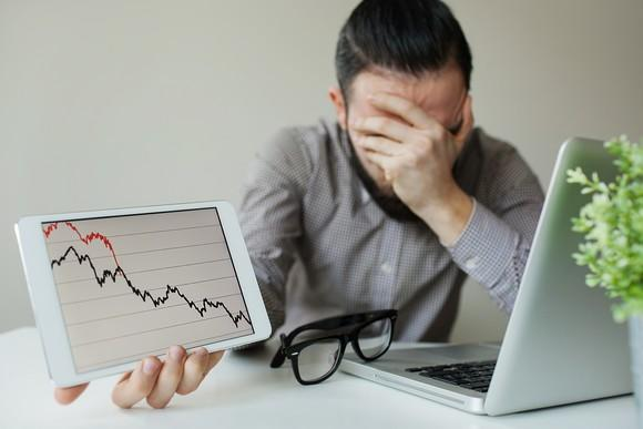 A frustrated man with his hand over his face, holding up a tablet with a plunging stock chart in his other hand.