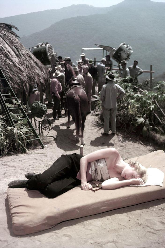 <p>During a break, Grace Kelly takes a nap in the sun on the set of <em>Mogambo</em>, a movie she starred in alongside Lauren Bacall and Humphrey Bogart.</p>