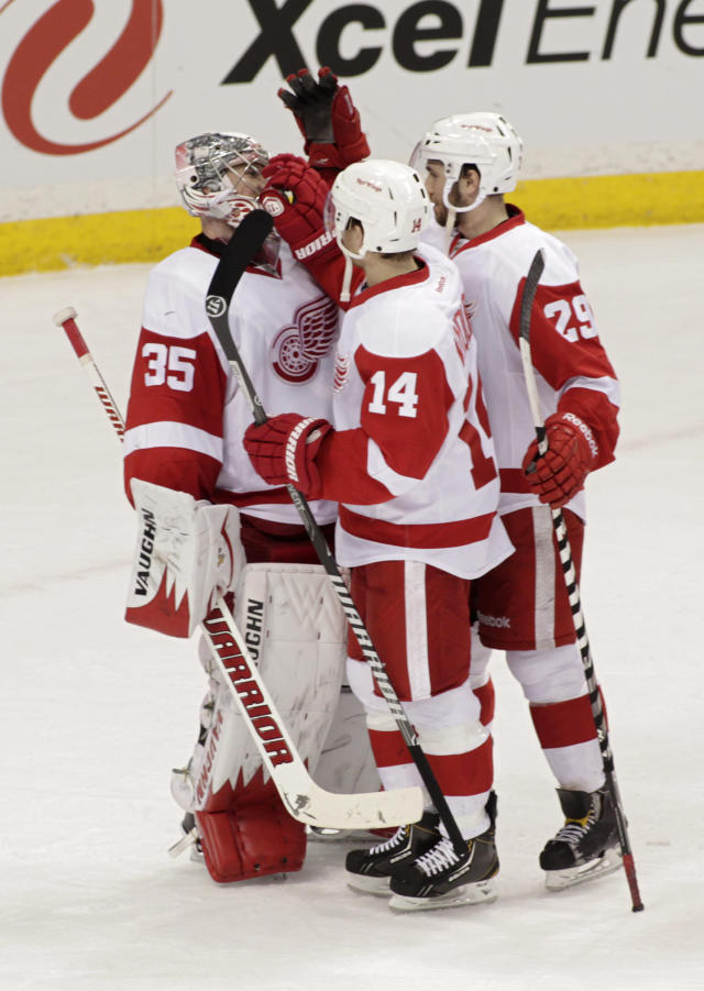 Detroit Red Wings goalie Jimmy Howard (35) is congratulated by teammates Gustav Nyquist, of Sweden (14) and Landon Ferraro (29) after they beat the Minnesota Wild 3-2 in an NHL hockey game, Saturday, March 22, 2014, in St. Paul, Minn. (AP Photo/Paul Battaglia)