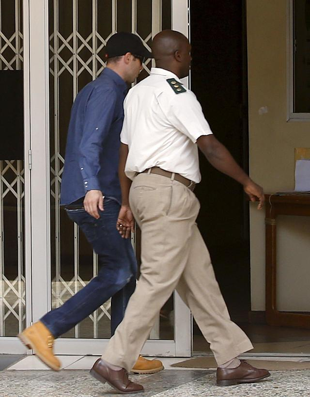 Oscar Pistorius (L) is escorted by correctional services officials as he arrives to get an electronic tag after he was granted bail in Pretoria, South Africa, December 8, 2015. REUTERS/Siphiwe Sibeko