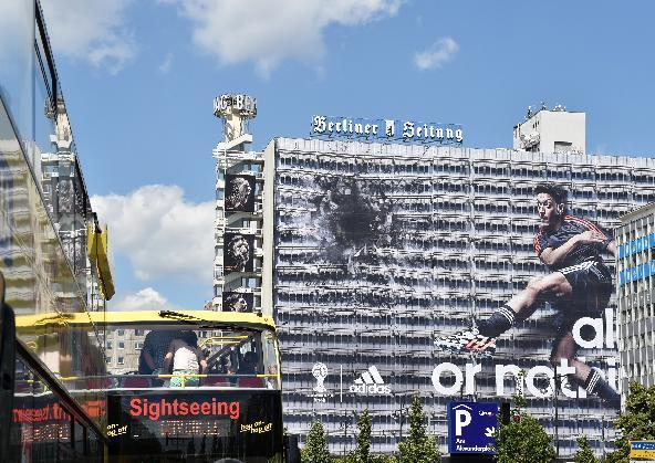 German national soccer player Mesut Ozil is visible on the facade of a publisher's building at Alexanderplatz square inBerlin, Germany, Friday June 6, 2014. Sportswear manufacturer Adidas has put up the advertisement on the entire facade of the building prior to the soccer WCup tournament in Brazil. (AP Photo/dpa,Jens Kalaene)