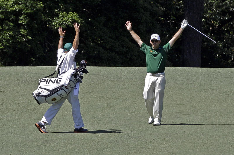 Louis Oosthuizen, of South Africa, and his caddie Wynand Stander react after Oosthuizen's double eagle two on the par 5 second hole during the fourth round of the Masters golf tournament Sunday, April 8, 2012, in Augusta, Ga. (AP Photo/Matt Slocum)