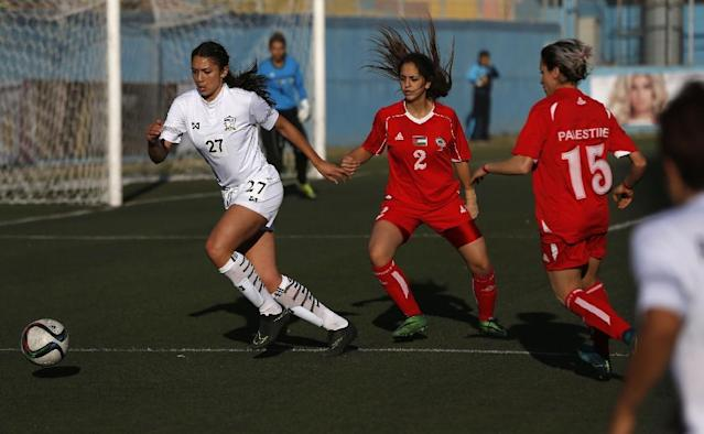 A Palestinian woman challenges a Thai player for the ball during a qualifying match for the Asian Cup on April 3, 2017 (AFP Photo/ABBAS MOMANI)