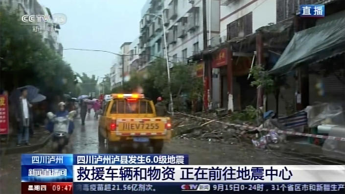 In this image made from video run by China's CCTV, people walk by damaged shophouses following an earthquake in Luxian County, southwest China's Sichuan Province, Thursday, Sept. 16, 2021. Rescue work was underway following the magnitude-6.0 earthquake. (CCTV via AP)