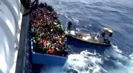 Still image from video shows a boat full of migrants next to Swedish ship Poseidon during a rescue operation in the sea off the coast of Libya