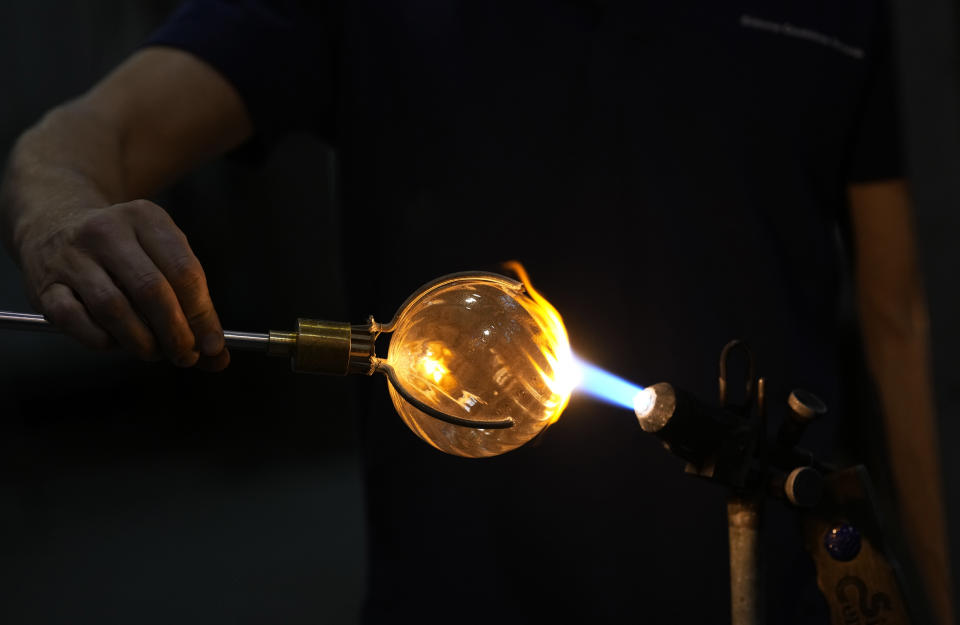 A glass-worker gives the last touch to a glass creation in a factory in Murano island, Venice, Italy, Thursday, Oct. 7, 2021. The glassblowers of Murano have survived plagues and pandemics and have transitioned to highly prized artistic creations to outrun competition from Asia, but surging energy prices may be their doom. (AP Photo/Antonio Calanni)