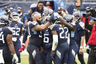 Tennessee Titans running back Derrick Henry (22) is mobbed by teammates after Henry scored the winning touchdown against the Houston Texans in overtime of an NFL football game Sunday, Oct. 18, 2020, in Nashville, Tenn. The Titans won 42-36. (AP Photo/Wade Payne)