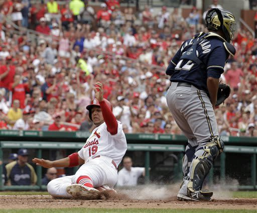 St. Louis Cardinals' Jon Jay, left, scores on a bunt-single by Pete Kozma as Milwaukee Brewers catcher Martin Maldonado, right, stands by during the fourth inning of a baseball game on Sunday, May 19, 2013, in St. Louis. (AP Photo/Jeff Roberson)