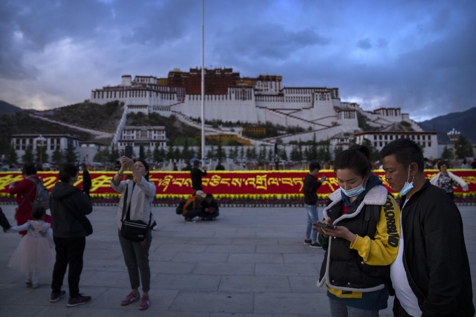Visitors gather on a public square at the base of the Potala Palace in Lhasa in western China's Tibet Autonomous Region, as seen during a rare government-led tour of the region for foreign journalists, Tuesday, June 1, 2021. Long defined by its Buddhist culture, Tibet is facing a push for assimilation and political orthodoxy under China's ruling Communist Party. (AP Photo/Mark Schiefelbein)