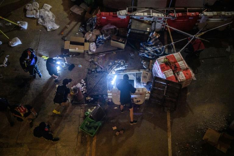 Protesters have removed metal manholes, some making exploratory forays into the fetid tunnels (AFP Photo/Anthony WALLACE)