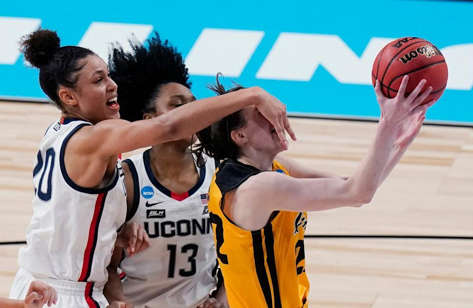 Iowa guard Caitlin Clark, right, is fouled by UConn forward Olivia Nelson-Ododa (20) as she tires to score during the second half.