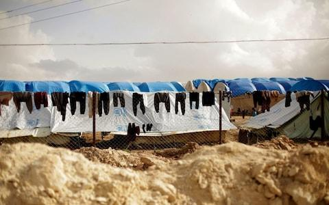 In this March 31, 2019, photo, laundry dries on a chain-link fence at Al-Hol camp, in the section where foreign families from Islamic State-held areas are housed, Hassakeh province, Syria - Credit: Maya Alleruzzo/AP