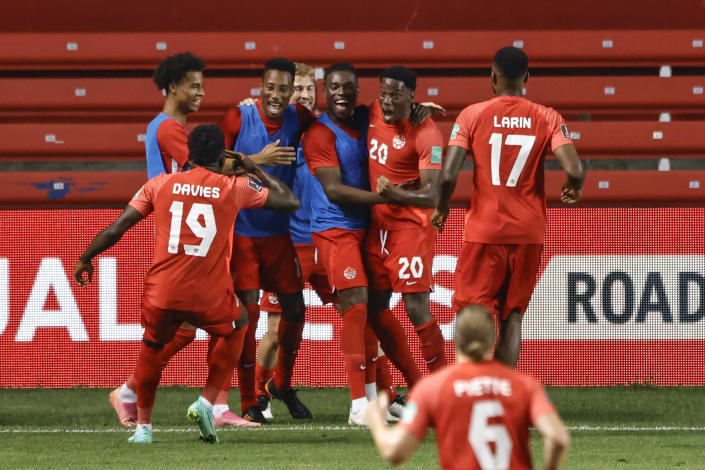 Canada's Jonathan David (20) celebrates with teammates after scoring a goal against Suriname during the second half of a World Cup 2022 Group B qualifying soccer match Tuesday, June 8, 2021, in Bridgeview, Ill. (AP Photo/Kamil Krzaczynski)