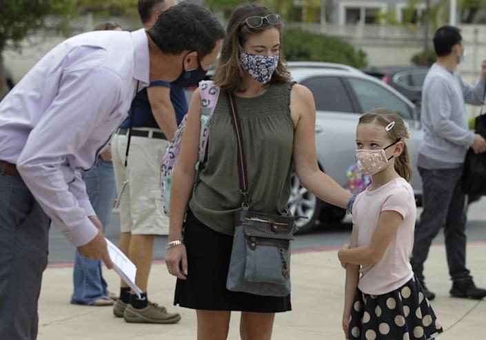 """Principal Ryan Stanley, left, welcomes second-grader Maeva Chappaz, with her mother, Amelie Chappaz, upon arrival for her first day of in-class instruction at Ocean Air School in the Del Mar Union School District. <span class=""""copyright"""">( Bill Wechter / San Diego Union-Tribune)</span>"""