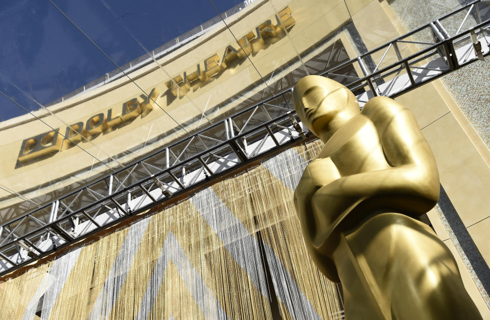 FILE - In this Feb. 24, 2016, file photo, an Oscar statue is pictured underneath the entrance to the Dolby Theatre in Los Angeles. When the Oscars broadcast begins April 25 on ABC, there won't be an audience. The base of the show won't be the Academy Awards' usual home, the Dolby Theatre (though the Dolby will still be involved), but Union Station, the airy, Art Deco-Mission Revival railway hub in downtown Los Angeles. For the producers, the challenges of COVID are an opportunity to, finally, rethink the Oscars. (Photo by Chris Pizzello/Invision/AP, File)