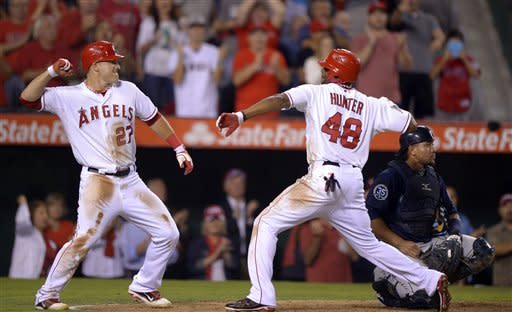 Los Angeles Angels' Torii Hunter, right, celebrates his two-run home run with teammate Mike Trout as Seattle Mariners catcher Miguel Olivo looks on during the fifth inning of their baseball game, Tuesday, Sept. 25, 2012, in Anaheim, Calif. (AP Photo/Mark J. Terrill)