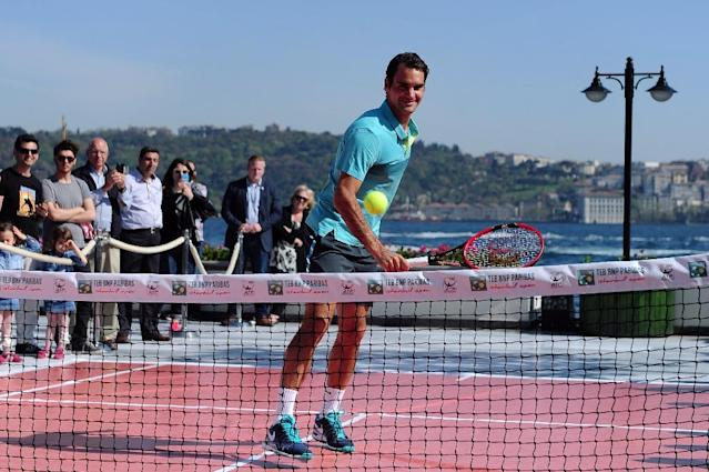 Swiss player Roger Federer returns the ball to a young Turkish tennis player during an exhibition tennis match after a press conference at the ATP Istanbul Open in Istanbul on April 27, 2015 (AFP Photo/Ozan Kose)