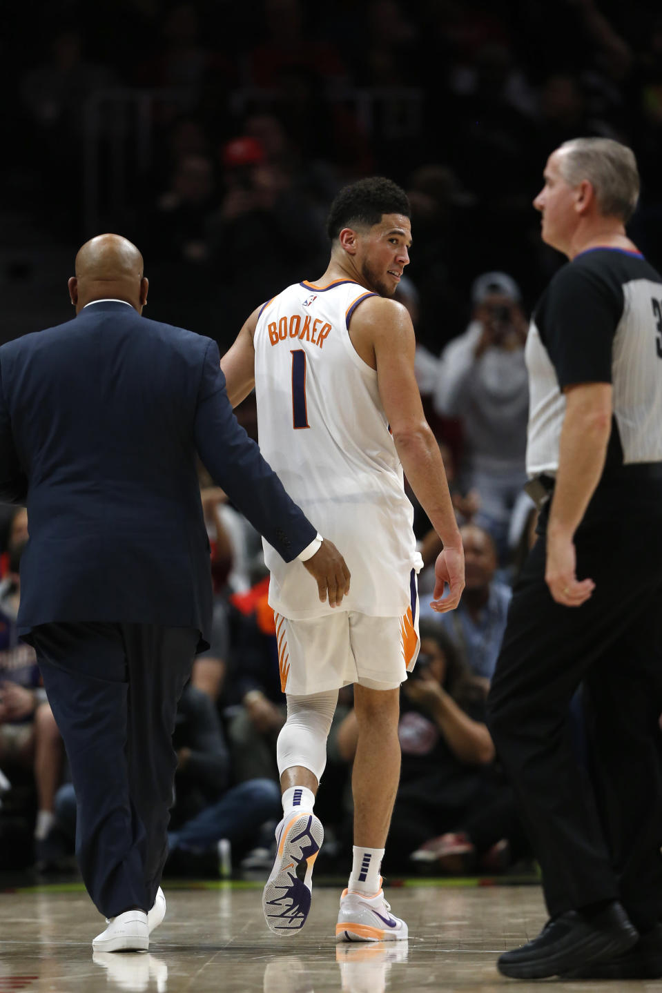 Phoenix Suns guard Devin Booker (1) looks back at an official as he leaves the court after being ejected in the second half of an NBA basketball game against the Atlanta Hawks Tuesday, Jan. 14, 2020, in Atlanta. The Hawks won 123-110. (AP Photo/John Bazemore)