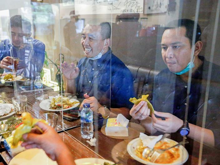 """People are seen at the Atjeh Connection restaurant with separation on the table in Jakarta, Indonesia, on June 8, 2020. <p class=""""copyright"""">REUTERS/Ajeng Dinar Ulfiana</p>"""