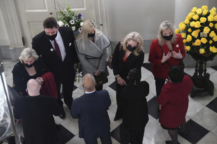 Top left, Patti Miller speaks with Gov. Larry Hogan as her husband, Senate President Emeritus Thomas V. Mike Miller, lies in state under the State House dome in Annapolis, Md., Thursday, Jan. 21, 2021. Standing next to Hogan talking with family members are Lt. Governor Boyd Rutherford, Yumi Hogan, the governor's wife, and House of Delegates Speaker Adrienne A. Jones. (Kim Hairston/The Baltimore Sun via AP, Pool)
