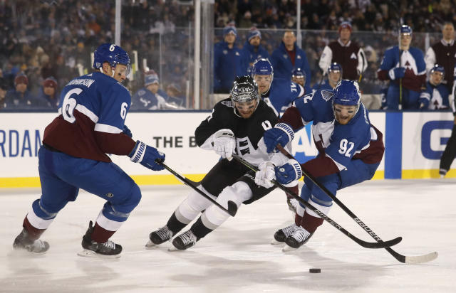 Los Angeles Kings center Adrian Kempe, left, loses control of the puck as he drives between Colorado Avalanche defenseman Erik Johnson, left, and left wing Gabriel Landeskog during the first period of an NHL hockey game Saturday, Feb. 15, 2020, at Air Force Academy, Colo. (AP Photo/David Zalubowski)