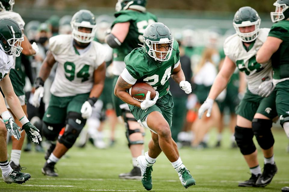 Michigan State running back Elijah Collins carries the ball during a spring practice session in East Lansing.