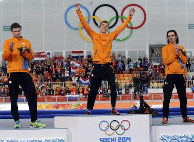 Athlethes for the Netherlands, gold medallist Jorrit Bergsma, center, raises his arms in celebration applauded by silver medallist Sven Kramer, left, and bronze medallist Bob de Jong of the Netherlands after the men's 10,000-meter speedskating race at the Adler Arena Skating Center during the 2014 Winter Olympics in Sochi, Russia, Tuesday, Feb. 18, 2014. (AP Photo/Patrick Semansky)