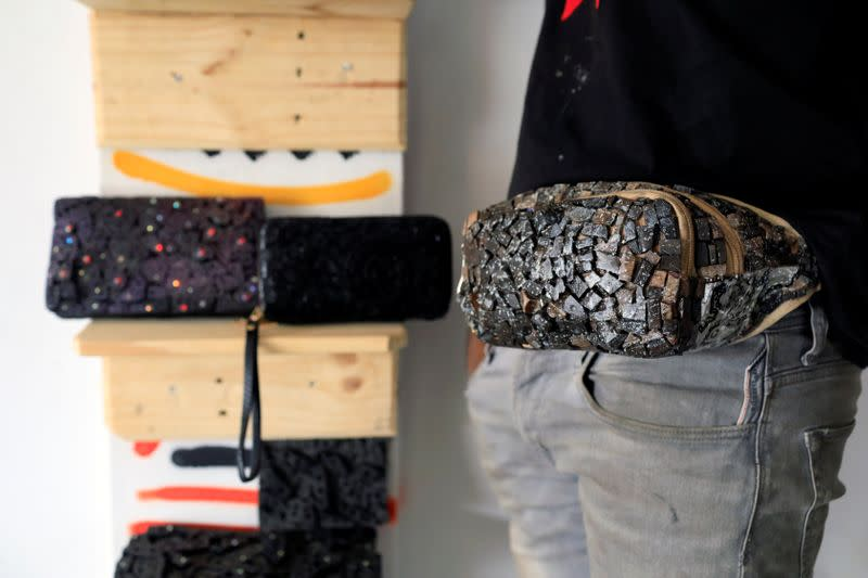 Visual artist Adeyemi Emmanuel samples a fanny pack he designed using pieces of wooden frames in his art studio in Lagos, Nigeria