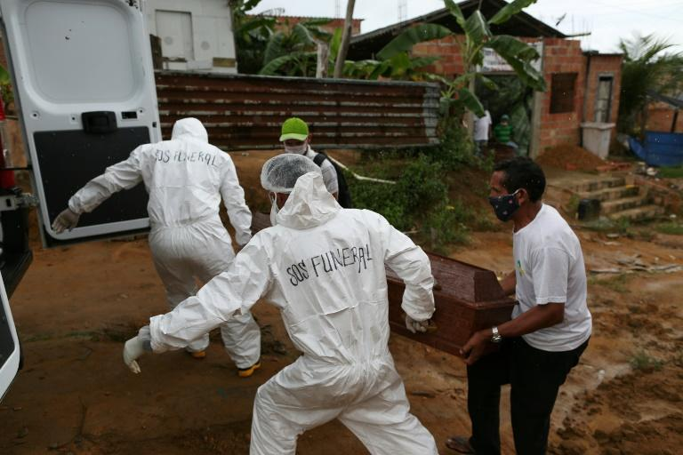 Manaus city workers remove the body of a 92-year-old man who died after showing symptoms of having contracted the COVID-19 novel coronavirus (AFP Photo/Michael DANTAS)
